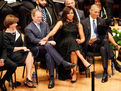 First lady Michelle Obama and President George W. Bush, flanked by President Barack Obama and former first lady Laura Bush, share a moment during a memorial service for five police officers were killed and several injured during a shooting in downtown Dallas last Thursday night, Tuesday, July 12, 2016, at the Morton H. Meyerson Symphony Center in Dallas. (AP Photo/Eric Gay)