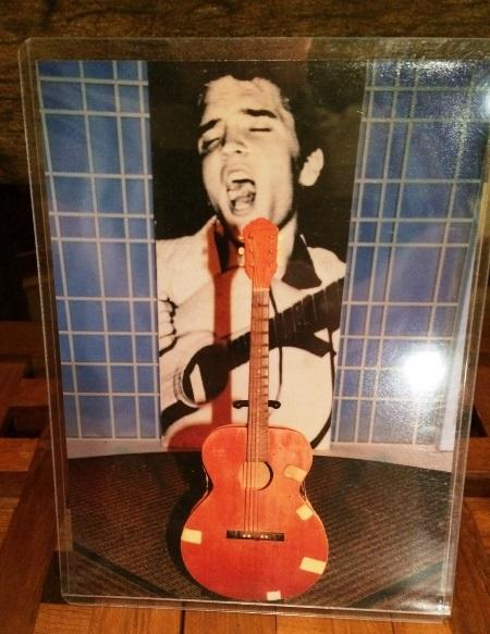 elvis-presleys-first-guitar-in-front-of-picture